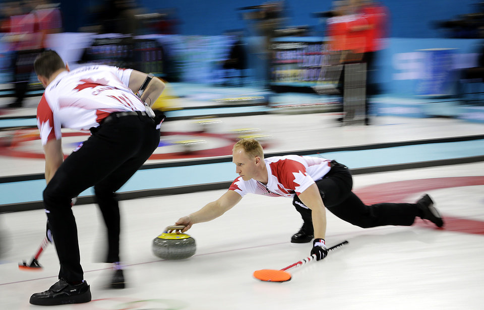 Photo - Canada's skip Brad Jacobs, right, delivers the rock while his teammate Ryan Harnden, Left, prepares to sweep the ice during the men's curling competition against Germany at the 2014 Winter Olympics, Monday, Feb. 10, 2014, in Sochi, Russia. (AP Photo/Wong Maye-E)