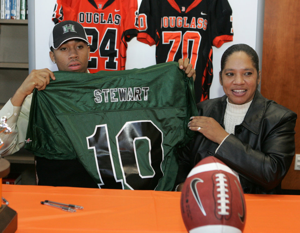 Photo - Douglass High School's Destin Stewart signs holds up a University of Hawaii jersey with his mother Sabena Watts looks on in Oklahoma City, Oklahoma February 4, 2009.  BY STEVE GOOCH, THE  OKLAHOMAN.  ORG XMIT: KOD
