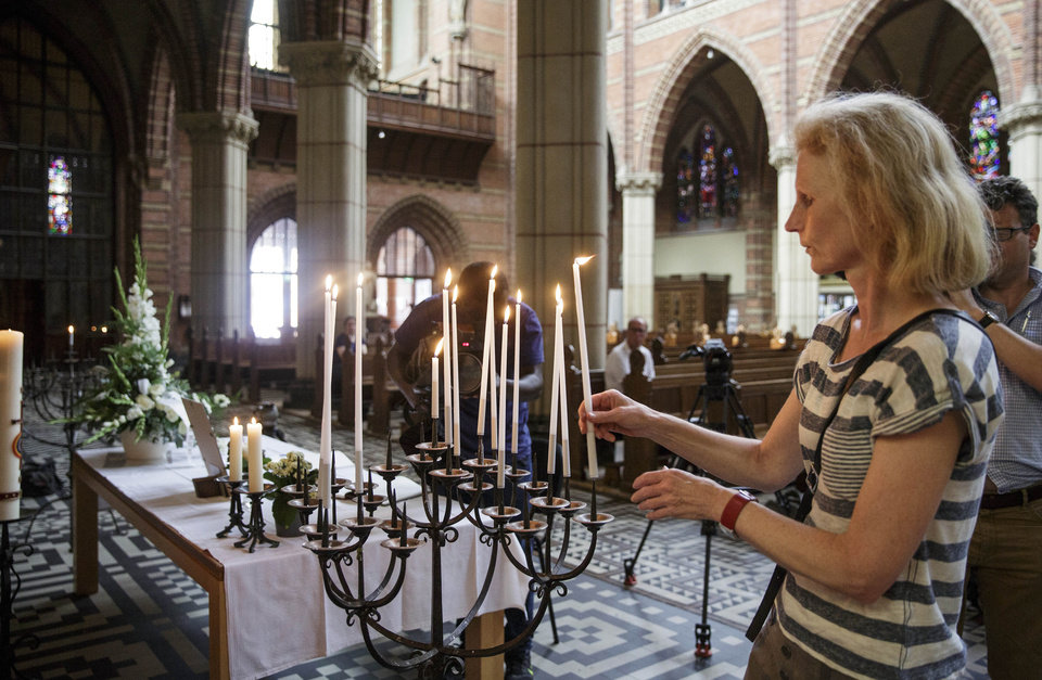 Photo - A woman lights a candle as people gather to commemorate victims of the Malaysia Airlines flight 17 which was shot down over Ukraine at St. Vitus church in Hilversum, Saturday, July 19, 2014. Three families living in Hilversum were among those killed when a Malaysian jetliner was shot down over Ukraine Thursday. All passengers, 298 people from nearly a dozen nations, more than half being Dutch were killed. Across the Netherlands, at sports clubs, schools and churches, friends met Saturday to console each another and attempt to come to terms with their loss. (AP Photo/Phil Nijhuis)