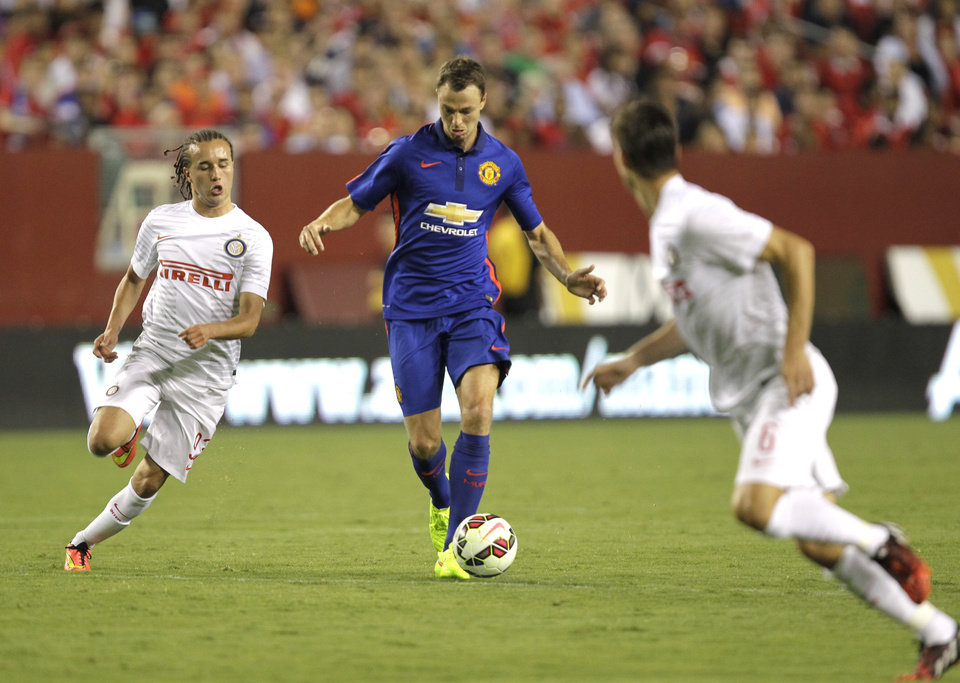 Photo - Manchester United's Jonny Evans, center, moves the ball as Inter Milan's Diego Laxalt, left, and Marco Andreolli (6) defend during the second half of the 2014 Guinness International Champions Cup soccer game, Tuesday, July 29, 2014, in Landover, Md. Manchester United won in a 5-3 penalty kick shootout. (AP Photo/Luis M. Alvarez)