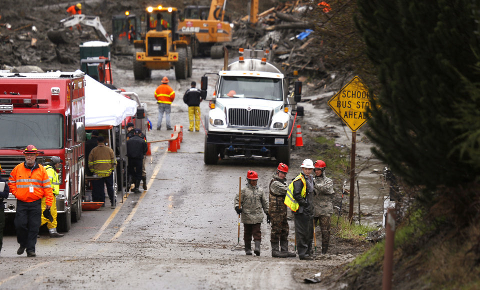 Photo - Searchers stand at the site of a deadly mudslide, Friday, March 28, 2014, in Oso, Wash. Besides the 26 bodies already found, dozens more people could be buried in the debris pile left from the mudslide nearly one week ago. (AP Photo/Lindsey Wasson, Pool)