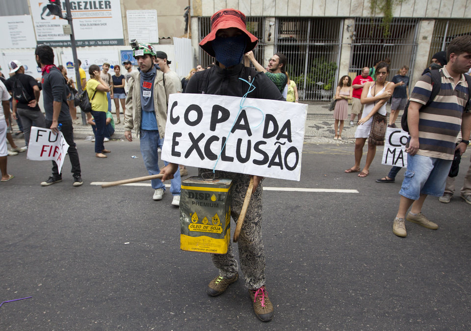 Photo - A demonstrator protests with a sing that reads in Portuguese,