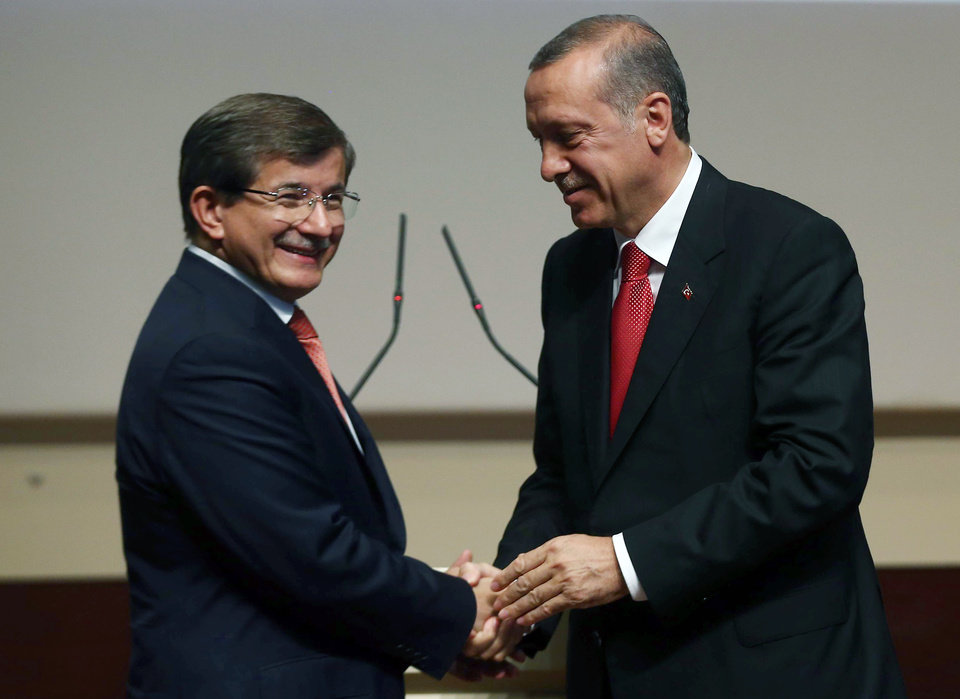 Photo - Turkey's president-elect Recep Tayyip Erdogan, right, greets Foreign Minister Ahmet Davutoglu after he announced Davutoglu as his ruling Justice and Development Party's new leader, in Ankara, Turkey, Thursday, Aug. 21, 2014.   Davutoglu, hand-picked by president-elect Erdogan to succeed him as prime minister, is expected to accept the largely backseat role although he is known to be an ambitious politician. (AP Photo/Burhan Ozbilici)