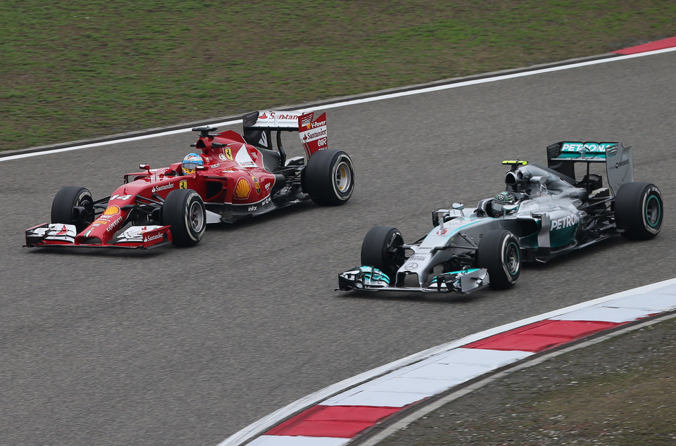 Photo - Ferrari driver Fernando Alonso of Spain, left, and Mercedes driver Nico Rosberg of Germany, right, drive their cars during the practice session for Sunday's Chinese Formula One Grand Prix at Shanghai International Circuit in Shanghai, Friday, April 18, 2014. (AP Photo/Eugene Hoshiko)