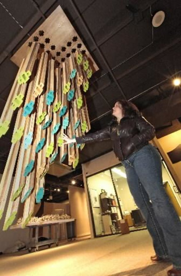 """Beatriz Mayorca uses her hand to make her wind chimes, titled """"Free Fall,"""" work while setting up for """"Soundscapes"""" at Science Museum Oklahoma.Photo By David McDaniel, The Oklahoman"""