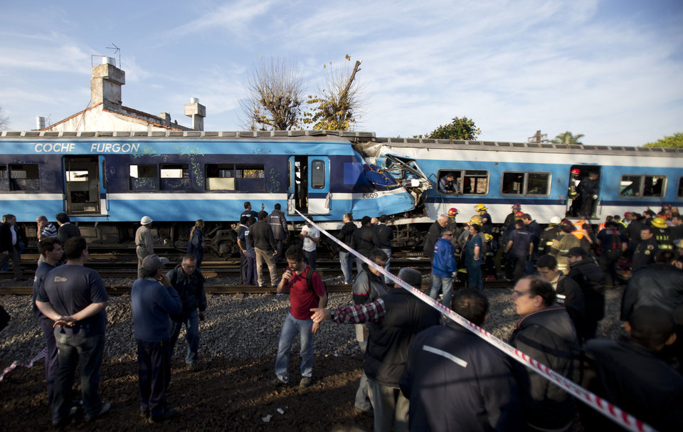 "Firefighters and rescue workers respond to a fatal commuter train wreck on the outskirts of Buenos Aires, Argentina, Thursday, June 13, 2013. A two-level train slammed into another that had stopped between stations during the morning commute Thursday. Firefighters and police are pulling passengers from the wreckage. Train operator spokesman Pablo Gunning says there are ""various fatalities"" though has not specified how many. (AP Photo/Natacha Pisarenko)"
