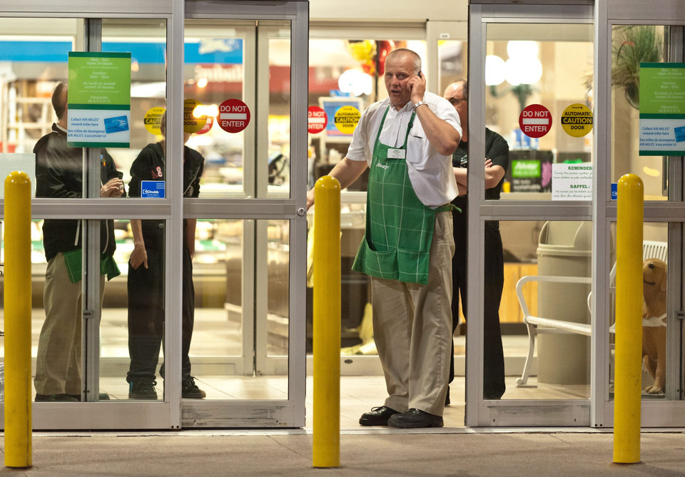Photo - Employees of a grocery store lock down their store in Moncton, New Brunswick, on Wednesday, June 4, 2014. Police in New Brunswick were searching Wednesday for an armed man after at least two people, both police officers, were injured in a shooting. The Royal Canadian Mounted Police in New Brunswick said on its Twitter feed that they were looking for 24-year-old Justin Bourque of Moncton who is considered armed and dangerous. The police force tweeted an image of a suspect wearing military camouflage and wielding two guns. (AP Photo/The Canadian Press, Marc Grandmaison)