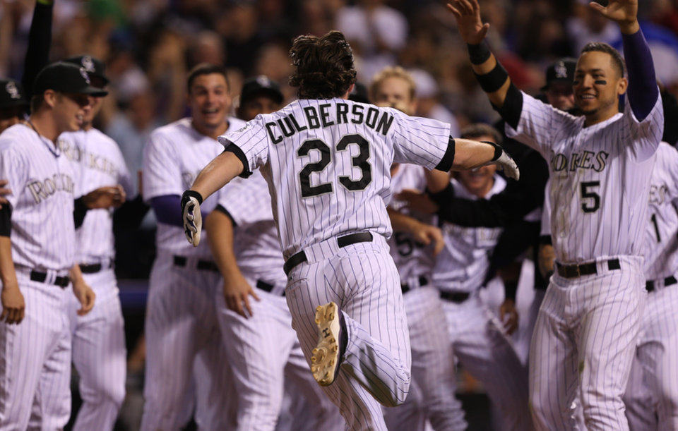 Photo - As teammates gather at home plate, Colorado Rockies' Charlie Culberson heads in to score after hitting a two-run, walkoff home run against the New York Mets in the ninth inning of the Rockies' 11-10 victory in a baseball game in Denver on Saturday, May 3, 2014. (AP Photo/David Zalubowski)