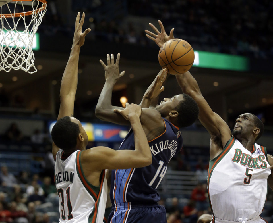 Photo - Charlotte Bobcats' Michael Kidd-Gilchrist (14) shoots between Milwaukee Bucks' John Henson (31) and Ekpe Udoh (5) during the first half of an NBA basketball game on Saturday, Nov. 23, 2013, in Milwaukee. (AP Photo/Morry Gash)