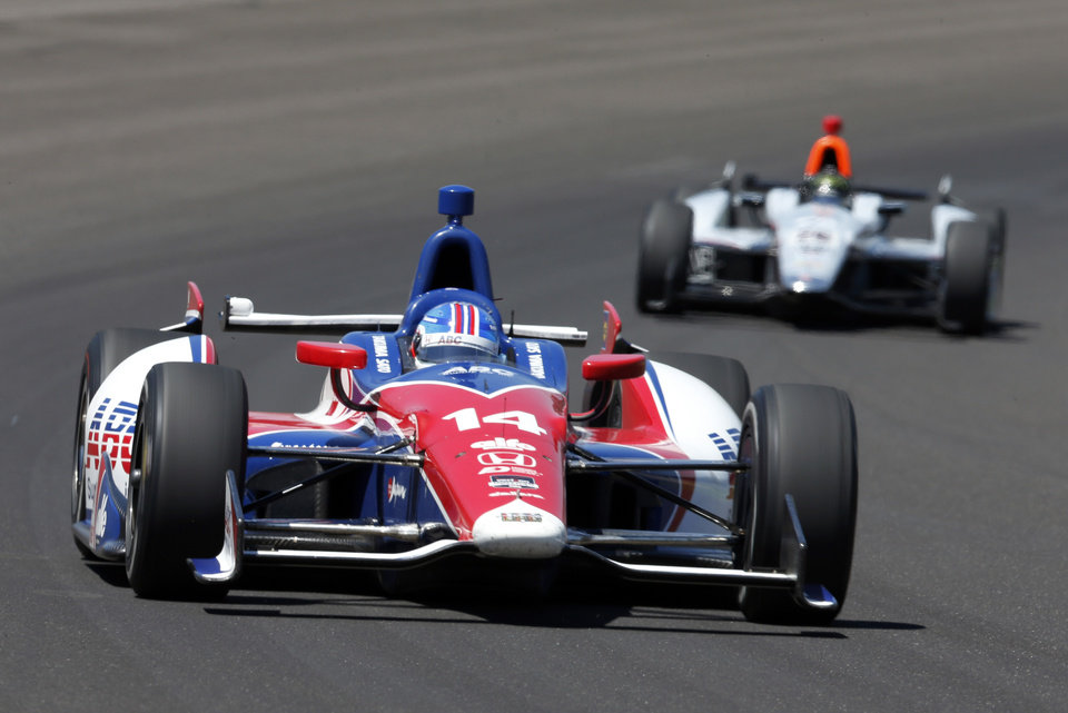 Photo - Takuma Sato, of Japan, leads Kurt Busch through the first turn during the Indianapolis 500 IndyCar auto race at the Indianapolis Motor Speedway in Indianapolis, Sunday, May 25, 2014. (AP Photo/Tom Strattman)