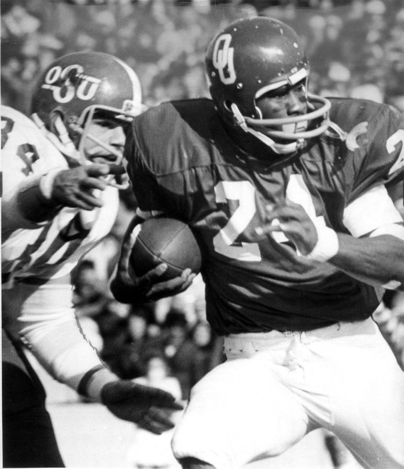Photo - OU's Joe Washington is about to be hit by OSU defender Mike Terry during the Bedlam college football game on Nov. 30, 1974. Oklahoma won, 44-13.  Staff photo by Jim Argo