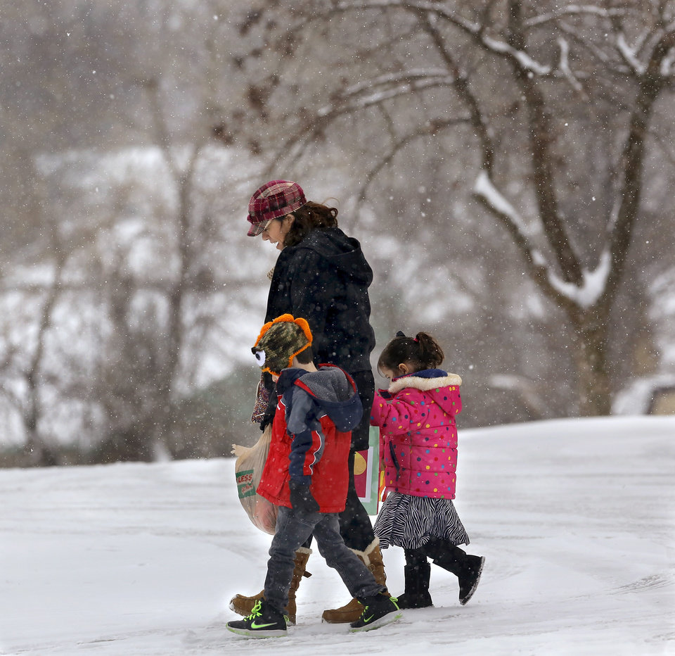 Photo - A woman and two young children walk across a parking lot in Midwest City. Snow began falling in central Oklahoma around 7 Sunday morning, Feb. 2, 2014.   Photo by Jim Beckel, The Oklahoman