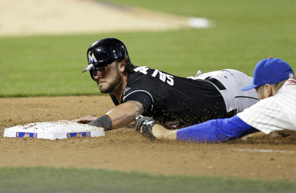 Photo - Miami Marlins' Jarrod Saltalamacchia (39) beats New York Mets first baseman Lucas Duda (21) back to first base after Garrett Jones lined out during the sixth inning of a baseball game, Saturday, April 26, 2014, in New York. (AP Photo/Frank Franklin II)