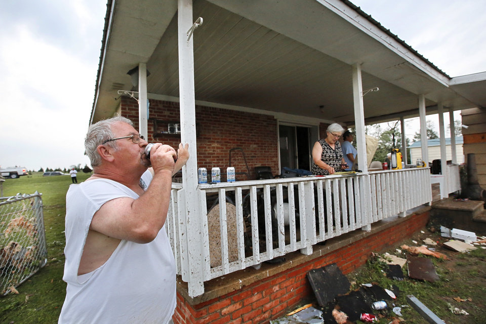 Photo - Wesley Little takes a drink from a beer can while standing near the front porch of his family's home about an hour after it was heavily damaged by a tornado.  His wife, Barbara, is on the porch, searching through a phone book for they number of their insurance agent. Little and his wife  have lived in this home for 25 years. Wesley and Barbara took shelter in their home's basement with 6 other people, including his mother, Emma McAdams,  and four dogs. A tornado caused extensive damage along I-40 at the junction with  US 177 on the west side of Shawnee Sunday evening,  May 19,  2013.  Photo  by Jim Beckel, The Oklahoman.