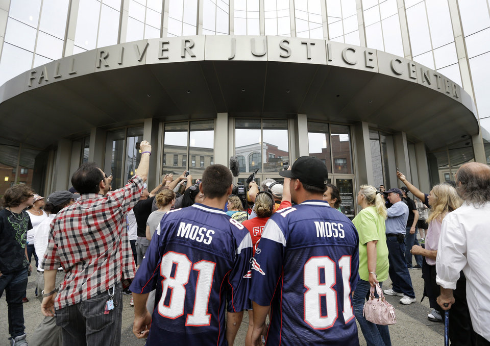 Photo - Interested bystanders and media members crowd around the entrance to the Fall River Justice Center after a bail hearing was held for former New England Patriots football player Aaron Hernandez in Fall River Superior Court Thursday, June 27, 2013 in Fall River, Mass. Hernandez, charged with murdering Odin Lloyd, a 27-year-old semi-pro football player, was denied bail. (AP Photo/Elise Amendola)