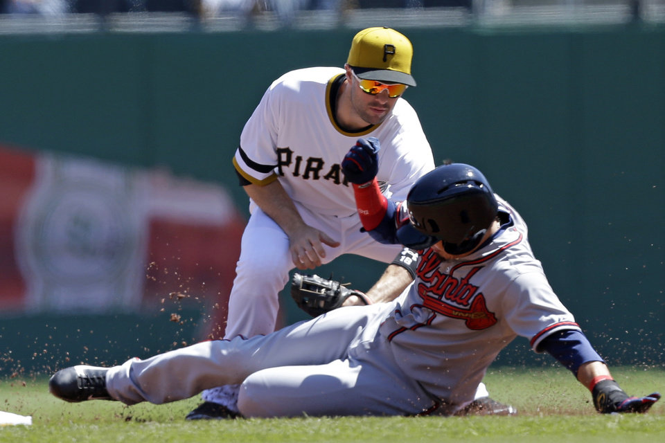 Pittsburgh Pirates second baseman Neil Walker, top, tags out Atlanta Braves' Ramiro Pena who was attempting to steal second during the first inning of a baseball game in Pittsburgh, Sunday, April 21, 2013. (AP Photo/Gene J. Puskar)