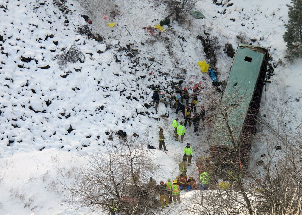 Photo - Emergency personnel respond to the scene of a multiple fatality accident where a tour bus careened through a guardrail along an icy Oregon highway and fell several hundred feet down a steep embankment, authorities said, Sunday, Dec. 30, 2012 about 15 miles east of Pendleton, Ore. The charter bus carrying about 40 people lost control around 10:30 a.m. on the snow- and ice-covered lanes of Interstate 84, according to the Oregon State Police. (AP Photo/East Oregonian, Tim Trainor)