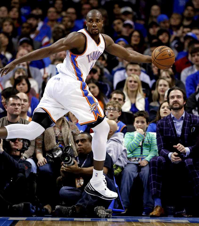 Photo - Thunder's Serge Ibaka (9) tries to save a ball from going out of bounds during the NBA basketball game between the Oklahoma City Thunder and the New Orleans Pelicans at Chesapeake Energy Arena on Dec. 21, 2014 in Oklahoma City, Okla. Photo by Steve Sisney, The Oklahoman