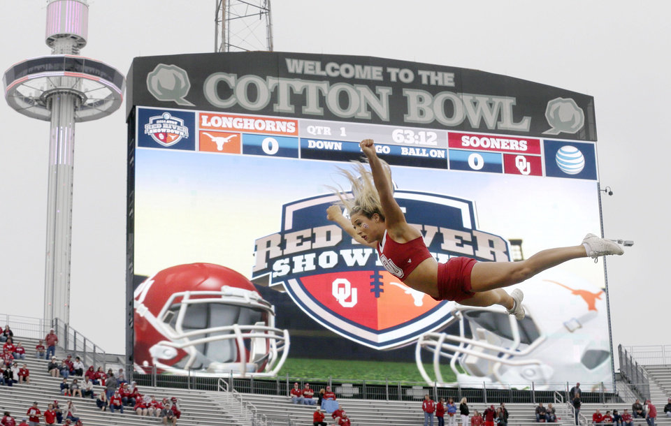 Photo -  An Oklahoma cheerleader flies in the air before the 2014 Red River game against Texas at the Cotton Bowl in Dallas. [AP PHOTO]