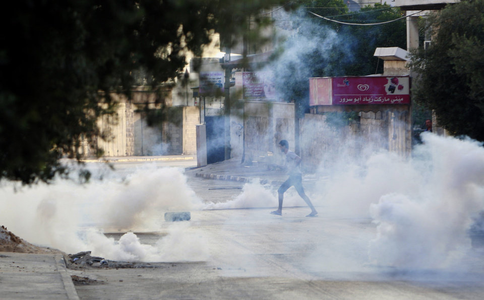 Photo - A Palestinian takes cover from tear gas fired by the Israeli troops during clashes with Palestinians in an early morning operation in the West Bank city of Jenin, Wednesday, July 2, 2014. Tensions have mounted between Israel and the Palestinians after the bodies of three Israeli teens were found in the West Bank more than two weeks after they went missing. (AP Photo/Mohammed Ballas)