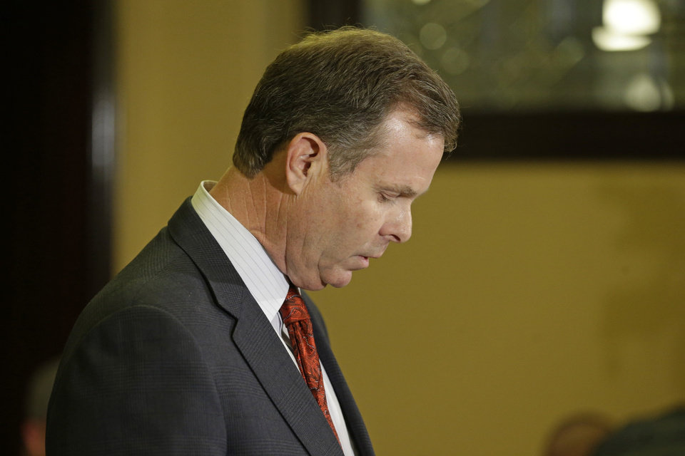 Photo - Utah Attorney General John Swallow looks down during a news conference Thursday, Nov. 21, 2013, in Salt Lake City. Swallow announced Thursday that he is stepping down amid multiple investigations of bribery and misconduct that have hounded him ever since he took office at the beginning of the year. (AP Photo/Rick Bowmer)