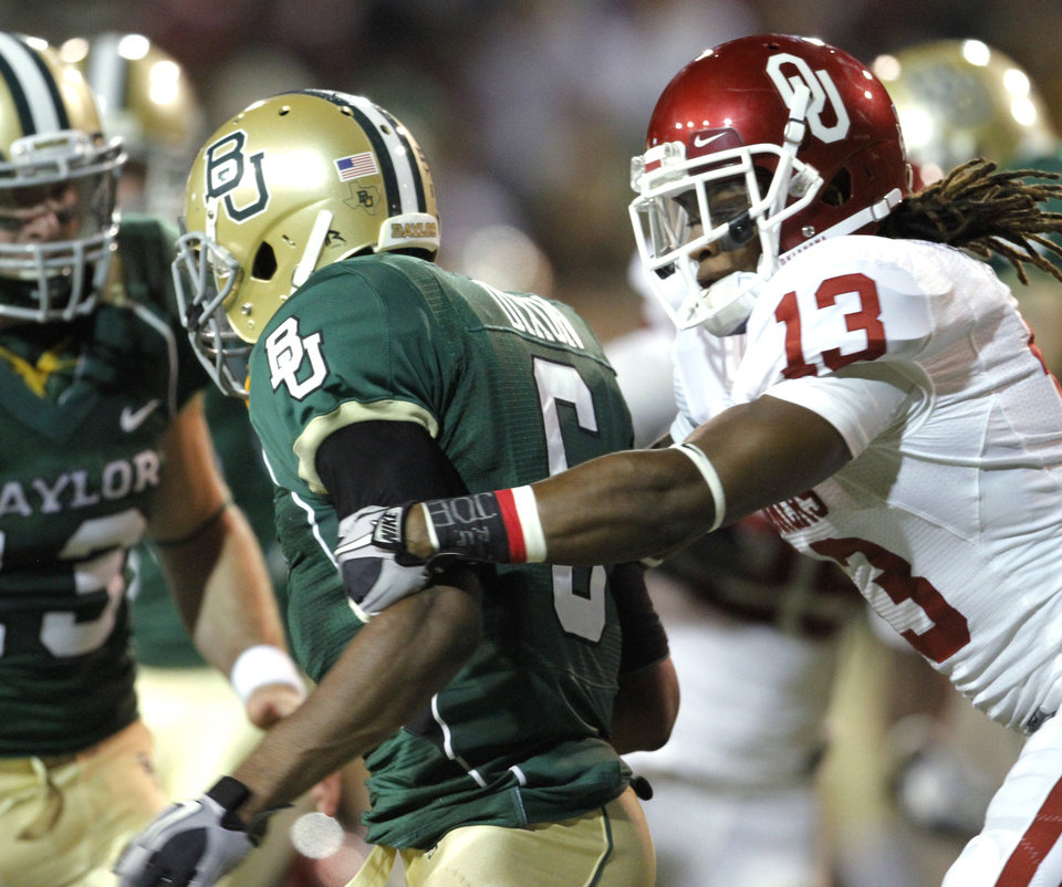 Photo - Sooner Marcus Trice (13) catches return man Ahmad Dixon (6) and causes a fumble through the end zone for a touchback during the second half of the college football game between the University of Oklahoma Sooners (OU) and the Baylor Bears (BU) at Floyd Casey Stadium on Saturday, November 20, 2010, in Waco, Texas.   Photo by Steve Sisney, The Oklahoman