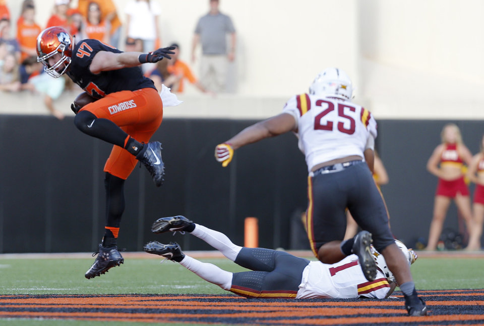 Photo - Oklahoma State's Blake Jarwin (47) leaps over Iowa State's D'Andre Payne (1) as Romelo Webster (27) also defends in the fourth quarter during a college football game between the Oklahoma State University Cowboys (OSU) and the Iowa State University at Boone Pickens Stadium in Stillwater, Okla., Saturday, Oct. 8, 2016. Photo by Sarah Phipps, The Oklahoman