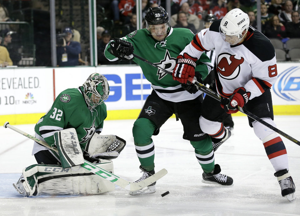 Photo - Dallas Stars' Kari Lehtonen (32), of Finland, attempts to reach a loose puck as Stars' Sergei Gonchar (55), of Russia, fights off pressure from New Jersey Devils' Dainius Zubrus (8), of Lithuania, in the second period of an NHL hockey game on Thursday, Jan. 30, 2014, in Dallas. (AP Photo/Tony Gutierrez)