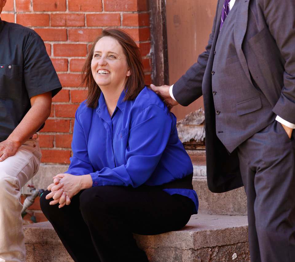 Photo - Defendant Bobbi Parker smiles while sitting on a step outside the jail with her husband and her defense attorney, Garvin Isaacs, right. The first full day of jury deliberations began Tuesday,  Sep. 20, 2011. after closing arguments were completed in the trial of Bobbi Parker late Monday night.  The trial is in the Greer County Courthouse in Mangum, Okla.  Photo by Jim Beckel, The Oklahoman