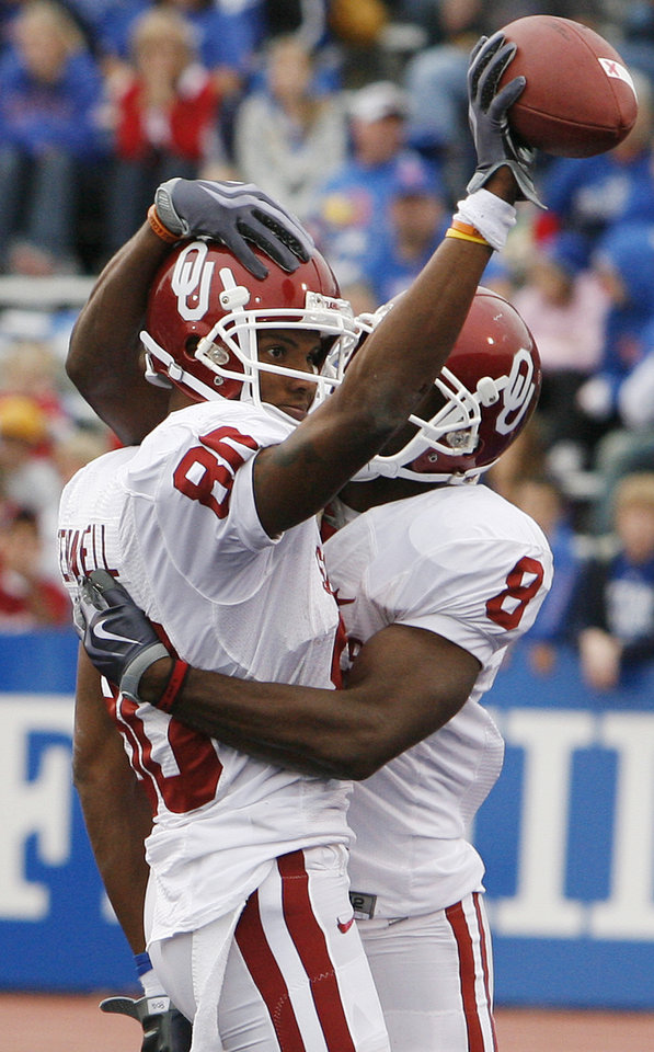 Photo - Oklahoma's Adron Tennell (80) and Brandon Caleb (8) celebrate after Tennell's touchdown during the second half of the college football game between the University of Oklahoma Sooners (OU) and the University of Kansas Jayhawks (KU) on Saturday, Oct. 24, 2009, in Lawrence, Kan. Oklahoma won the game 35-13. Photo by Chris Landsberger, The Oklahoman