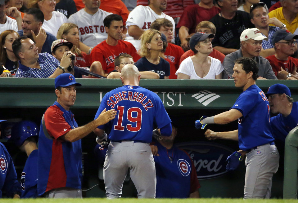 Photo - Chicago Cubs' Nate Schierholtz (19) is greeted at the dugout after his solo home run in the eighth inning of a baseball game against the Boston Red Sox at Fenway Park in Boston, Wednesday, July 2, 2014. (AP Photo/Elise Amendola)