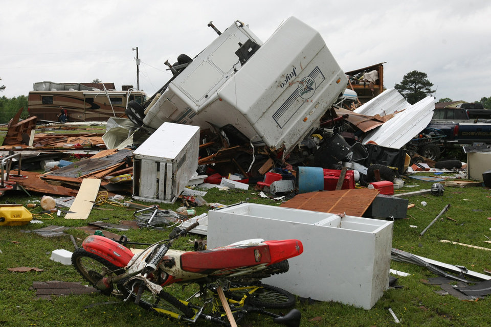 Photo - A camper is overturned among the damage to the home of Jerry Dye in the Brewer community  4 in Lee County near Tupelo, Miss.  Another night of severe weather has left four people dead in Mississippi, including a Louisiana police officer who was out camping with his daughter, raising the state's total death toll to at least five.  (AP Photo/The Northeast Mississippi Daily Journal, C. Todd Sherman)