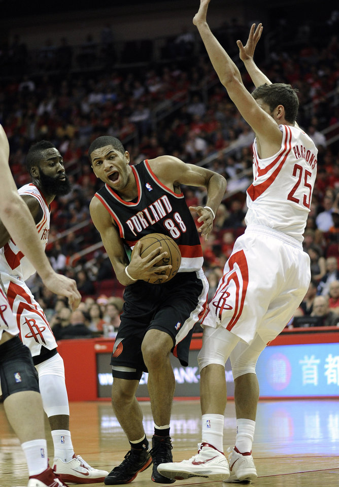 Portland Trail Blazers\' Nicolas Batum (88) makes his way between Houston Rockets defenders Chandler Parsons (25) and James Harden, left, in the first half of an NBA basketball game on Saturday, Nov. 3, 2012, in Houston. (AP Photo/Pat Sullivan)