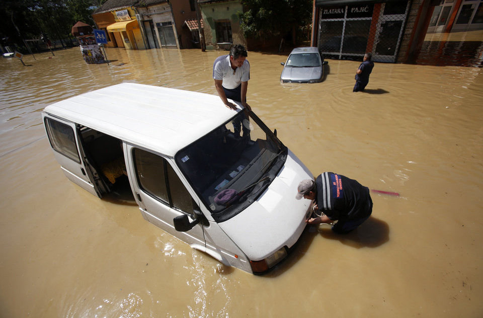 Photo - Two men trying to restart their van stuck in a flooded street in Obrenovac, some 30 kilometers (18 miles) southwest of Belgrade, Serbia, Monday, May 19, 2014. Belgrade braced for a river surge Monday that threatened to inundate Serbia's main power plant and cause major power cuts in the crisis-stricken country as the Balkans struggle with the consequences of the worst flooding in southeastern Europe in more than a century. At least 35 people have died in Serbia and Bosnia in the five days of flooding caused by unprecedented torrential rain, laying waste to entire towns and villages and sending tens of thousands of people out of their homes, authorities said. (AP Photo/Darko Vojinovic)