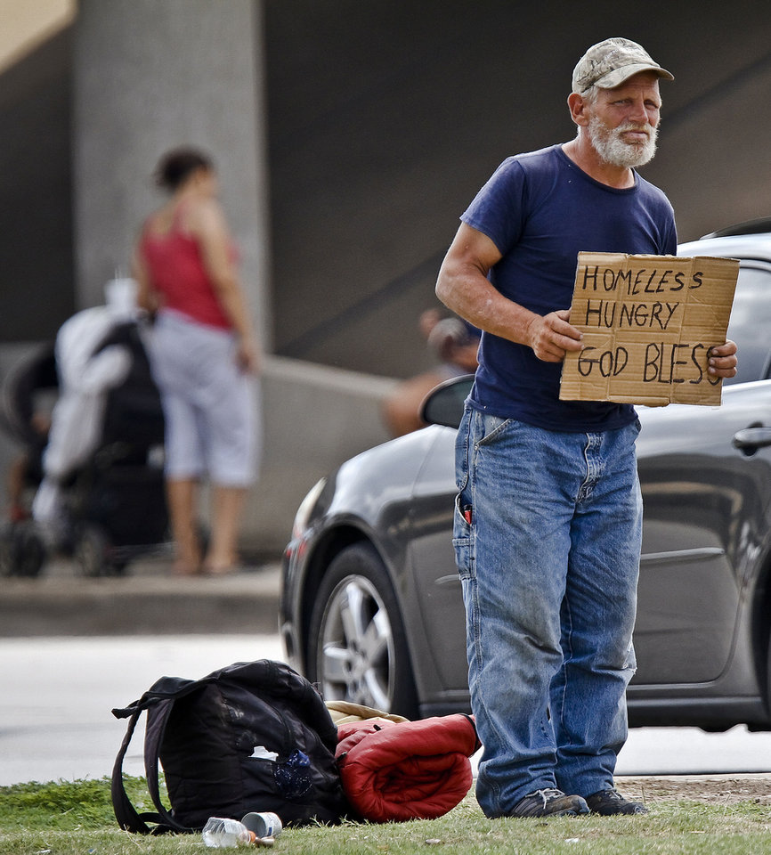Raymond Hauser, 50, of Joplin, Mo. holds his sign while standing next to his belongings as he panhandles the intersection at I-40 and MacArthur Blvd. on Wednesday, Sept. 26, 2012, in Oklahoma City, Okla. Hauser ended up in Oklahoma after being stranded while hitchhiking to California a month ago.  Photo by Chris Landsberger, The Oklahoman
