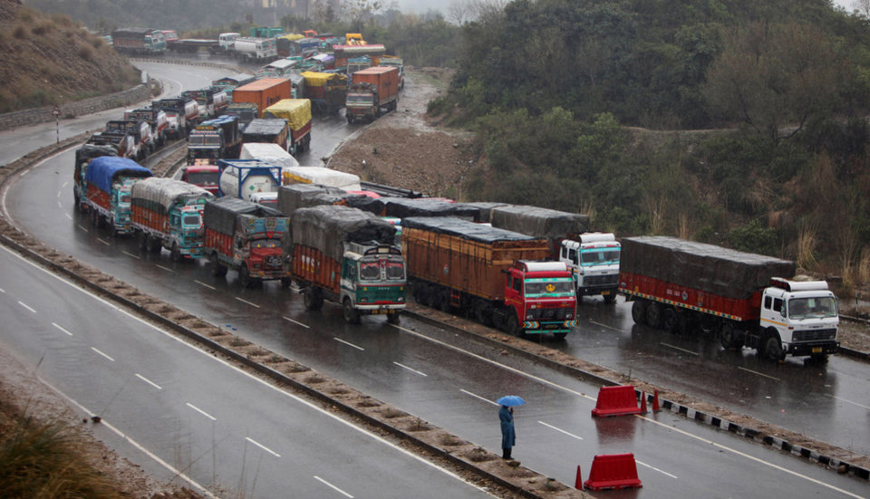 Stranded trucks wait for the Jammu-Srinagar highway to reopen on the outskirts of Jammu, India, Saturday, Feb.23, 2013. A fresh spell of rain and snow has blocked the road linking Jammu and Srinagar, the winter and summer capitals respectively of Indian Kashmir. (AP Photo/Channi Anand)