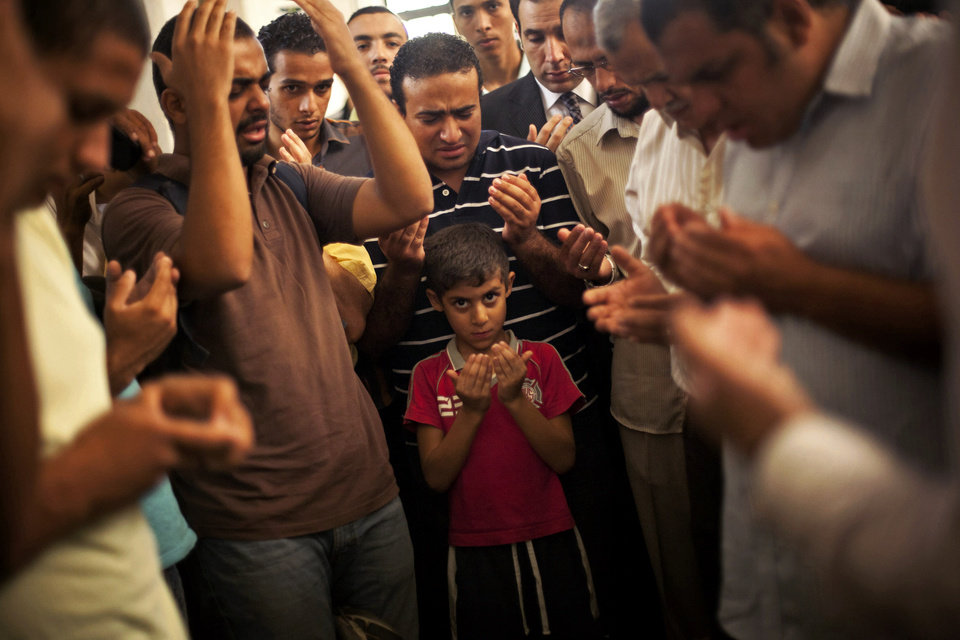 Photo - A son of the late Ammar Badie prays during his father's funeral in al-Hamed mosque in Cairo's Katameya district on Sunday, Aug. 18, 2013. Badie, the son of Muslim Brotherhood's spiritual leader Mohammed Badie, was killed by Egyptian security forces Friday during clashes in Cairo's Ramses Square. Egypt's military leader vowed Sunday that the army will not allow further violence after the deaths of hundreds in days of political unrest, while still calling for the political inclusion of Islamist supporters of the country's ousted president. (AP Photo/Manu Brabo)