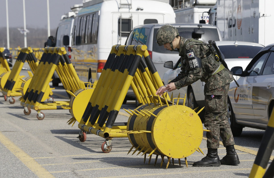 Photo - A South Korean soldier checks the id cards of members of media as their vehicles wait to enter at barricaded Unification Bridge near the border village of Panmunjom, that has separated the two Koreas since the Korean War, in Paju, north of Seoul, South Korea, Tuesday, April 9, 2013. North Korean workers didn't show up for work at a jointly run factory complex with South Korea on Tuesday, a day after Pyongyang suspended operations at the last remaining major economic link between rivals locked in an increasingly hostile relationship. (AP Photo/Lee Jin-man)