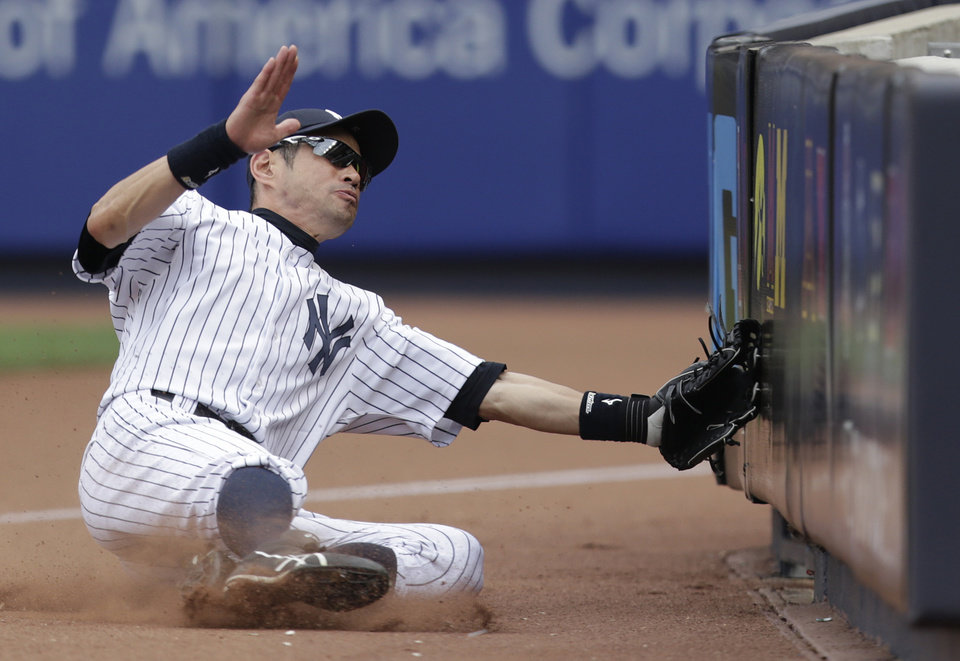 Photo - New York Yankees right fielder Ichiro Suzuki slides into a barrier on foul territory while chasing a foul ball by Cincinnati Reds' Neftali Soto during the ninth inning of an MLB baseball game, Saturday, July 19, 2014, at Yankee Stadium in New York. The Yankees won 7-1. (AP Photo/Julio Cortez)