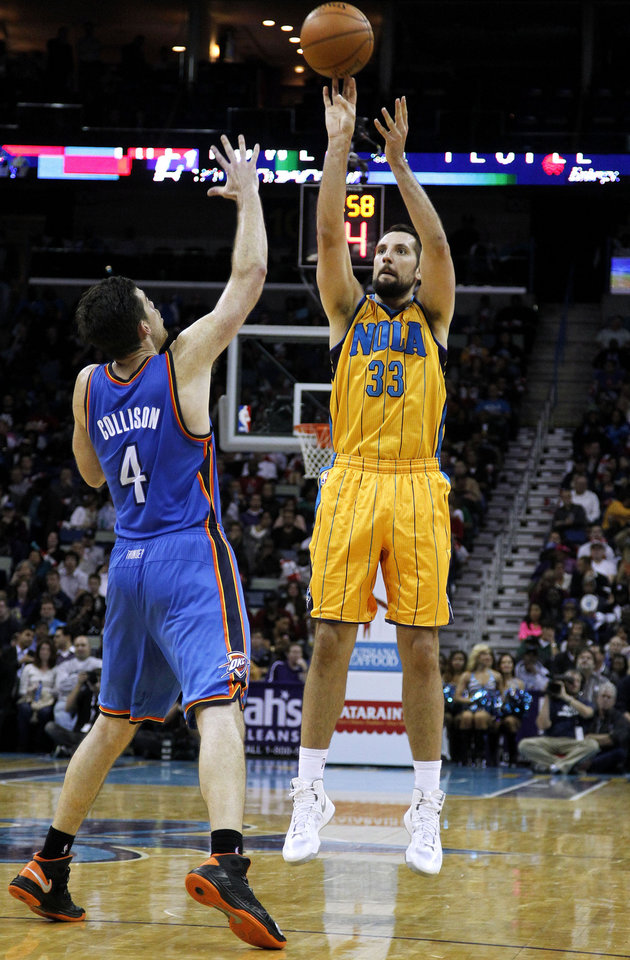 Photo - New Orleans Ryan Anderson (33) shoots the ball over Oklahoma City's Nick Collison (4) during the second half of an NBA basketball game in New Orleans, Friday, Nov. 16, 2012. The Thunder won 110-95. (AP Photo/Jonathan Bachman) ORG XMIT: LAJB113