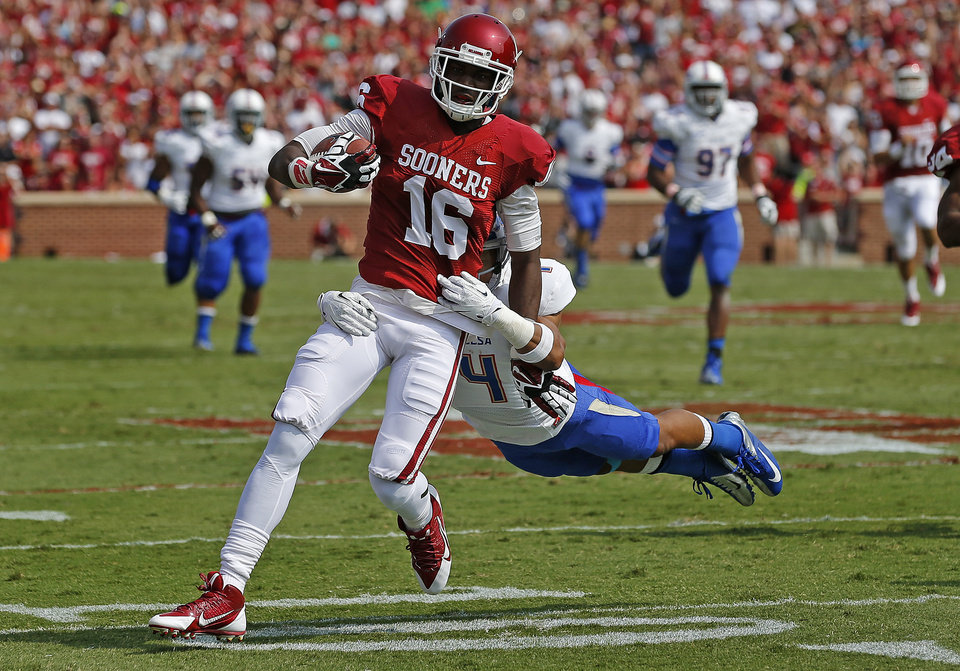 Photo - Oklahoma's Jaz Reynolds (16) tries to  fight off Tulsa's Darnell Walker (4) after a long reception during a college football game between the University of Oklahoma Sooners (OU) and the Tulsa Golden Hurricane at Gaylord Family-Oklahoma Memorial Stadium in Norman, Okla., on Saturday, Sept. 14, 2013. Oklahoma won 51-20. Photo by Bryan Terry, The Oklahoman