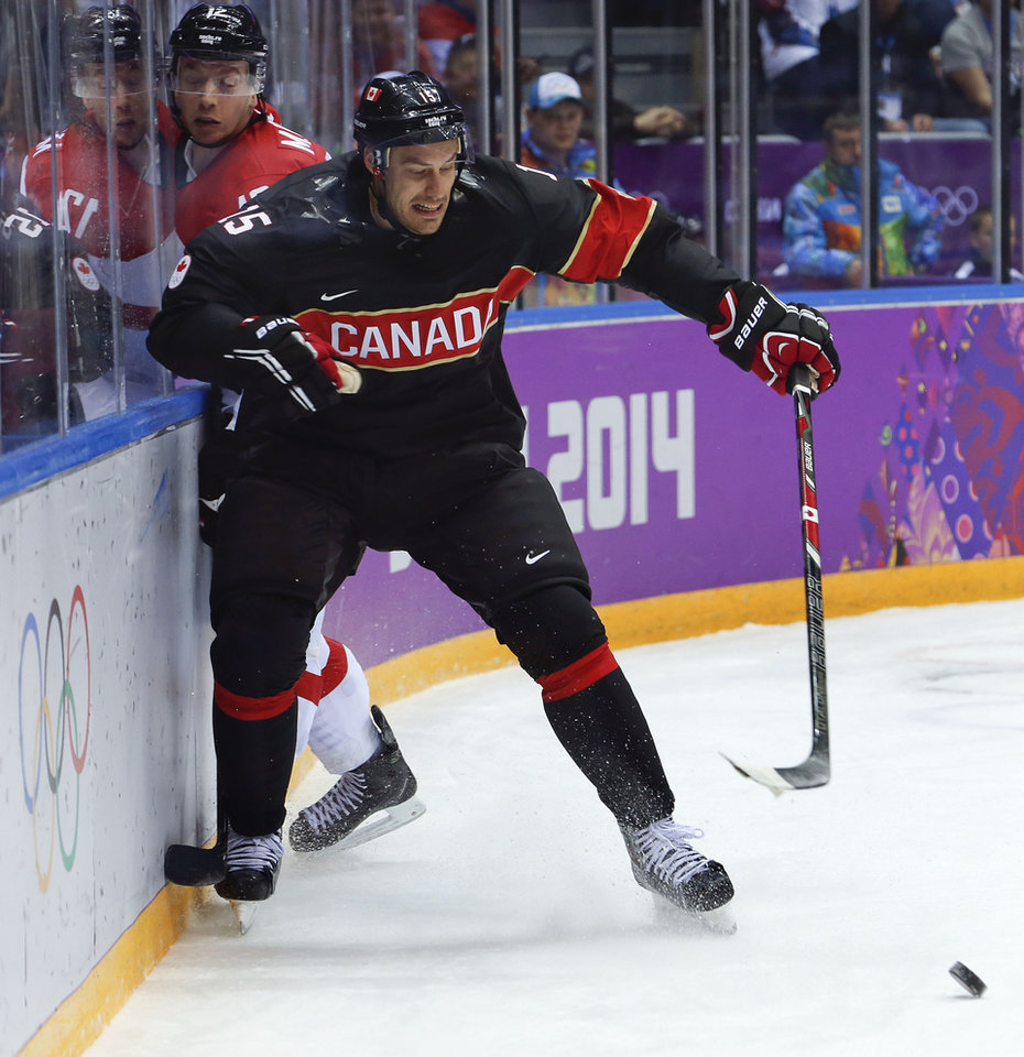 Photo - Canada forward Ryan Getzlaf seals off Austria forward Michael Raffl from the puck in the first period of a men's ice hockey game at the 2014 Winter Olympics, Friday, Feb. 14, 2014, in Sochi, Russia. (AP Photo/Mark Humphrey)