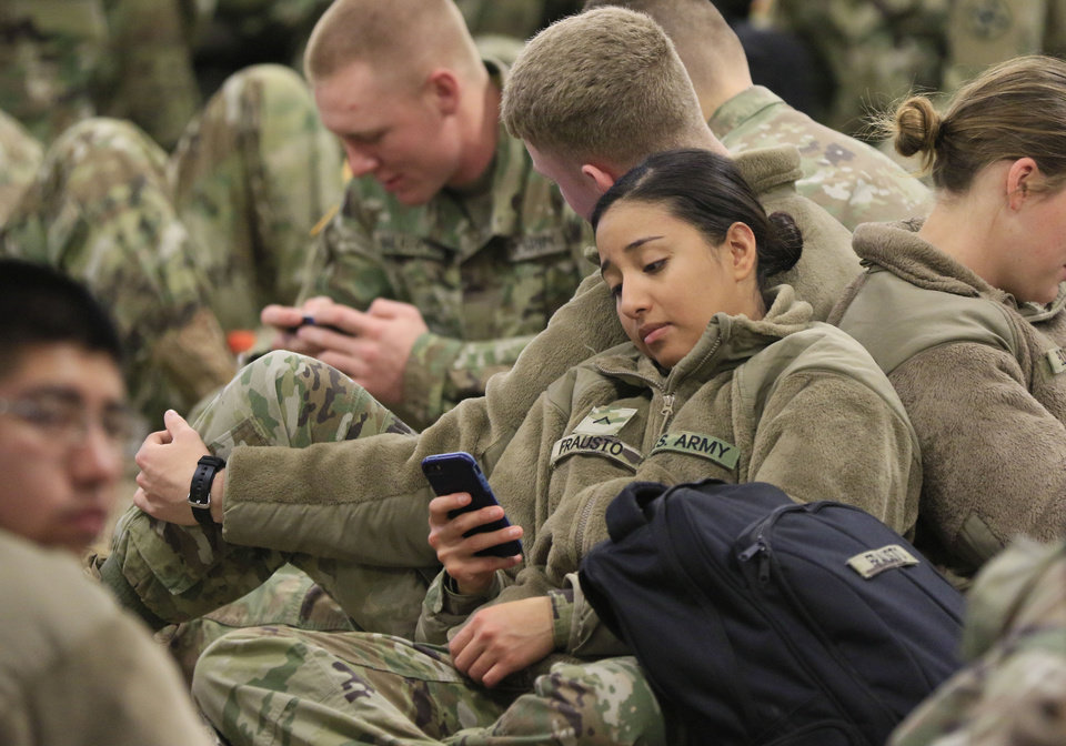 Photo -  Pvt. Claudia Frausto, of Beaverton, Ore., sends text messages Monday while waiting for her flight Monday morning at Will Rogers World Airport. Frausto was one of more than 3,000 soldiers based at Fort Sill who left the post this week on holiday leave. [Photo by Paul Hellstern, The Oklahoman]