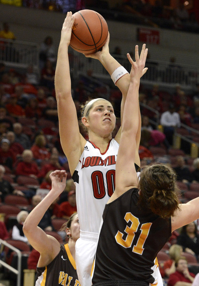 Photo - Louisville's Sara Hammond, left, gets a shot off over the defense of Valparaiso's Gina Lange during the second half of an NCAA women's college basketball game Saturday Dec. 8, 2012, in Louisville, Ky. Louisville defeated Valparaiso 96-40.  (AP Photo/Timothy D. Easley)