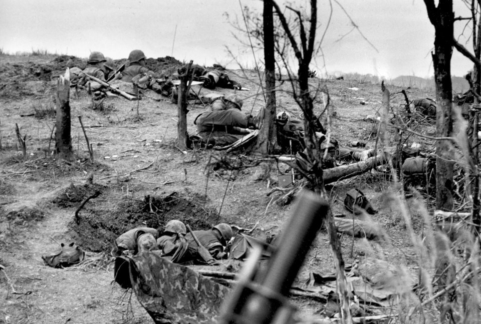 """Photo - FILE -In this March 3, 1967 file photo, U.S. Marines of the 1st Battallion, 9th Marines, crouch in the cover of their foxholes on barren and blasted hilltop 162, some three miles south of the DMZ, in Vietnam, as a mortar barrage from North Vietnamese forces hits their position. The Marine Corps is holding a deactivation ceremony on Friday, Aug. 29, 2014, for the 1st Battalion, 9th Marine Regiment, 2nd Marine Division, a battalion nicknamed the """"Walking Dead."""" (AP Photo/Kim Ki Sam, File)"""