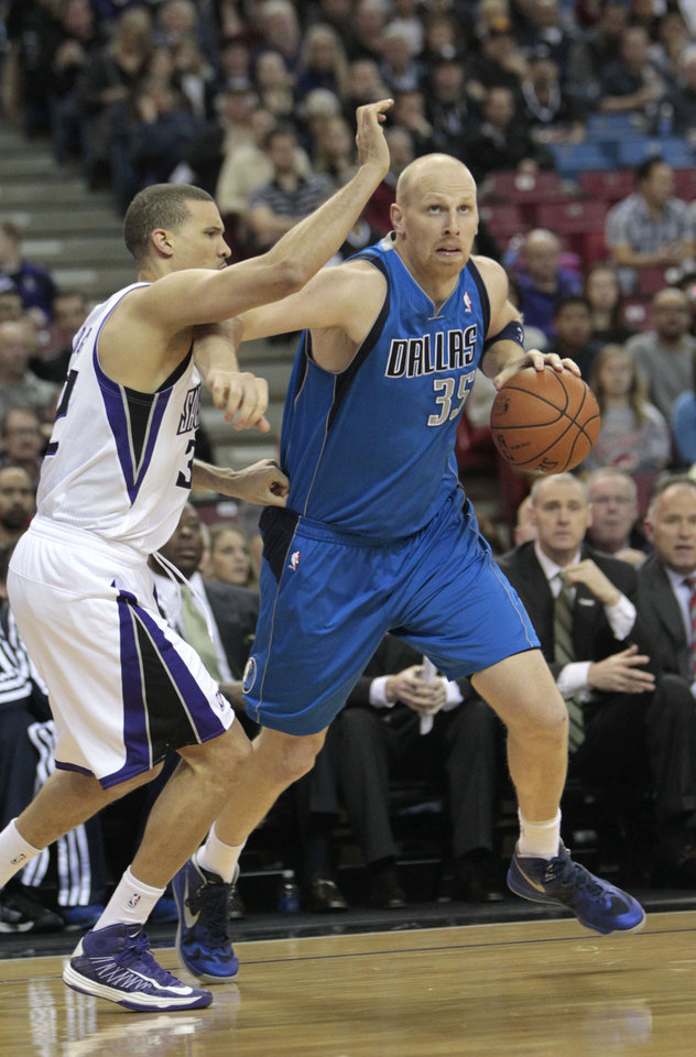 Dallas Mavericks center Chris Kaman, right, drives to the basket against Sacramento Kings forward Francisco Garcia during the first quarter of an NBA basketball game in Sacramento, Calif., Thursday, Jan. 10, 2013. (AP Photo/Rich Pedroncelli