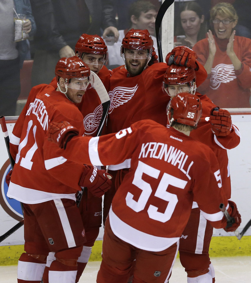 Photo - Detroit Red Wings, from left, Daniel Alfredsson, of Sweden; Tomas Jurco, of Slovakia; Riley Sheahan (15); Tomas Tatar (21), of the Czech Republic; and Niklas Kronwall,of Sweden celebrate Sheahan's goal during the third period of an NHL hockey game against the Carolina Hurricanes in Detroit, Friday, April 11, 2014. (AP Photo/Carlos Osorio)