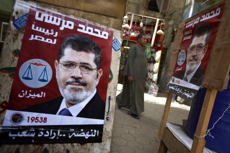Photo -   A man walks by posters of Muslim Brotherhood presidential candidate, Mohammed Morsi with Arabic that reads,