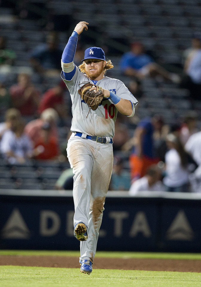 Photo - Los Angeles Dodgers third baseman Justin Turner (10) reacts after defeating the Atlanta Braves 6-2 in a baseball game  Monday, Aug. 11, 2014 in Atlanta.  (AP Photo/John Bazemore)