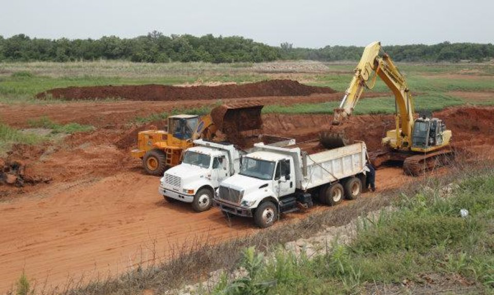 Photo - Oklahoma City Water Quality Department trucks move dirt at Lake Stanley Draper, where a $46 million renovation project has been in progress since August.  STEVE SISNEY - THE OKLAHOMAN